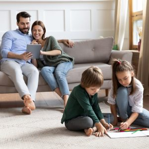 Cute little brother and sister sit on floor drawing in album, young parents relax on comfortable couch in living room using tablet, young Caucasian family rest together enjoy leisure weekend at home